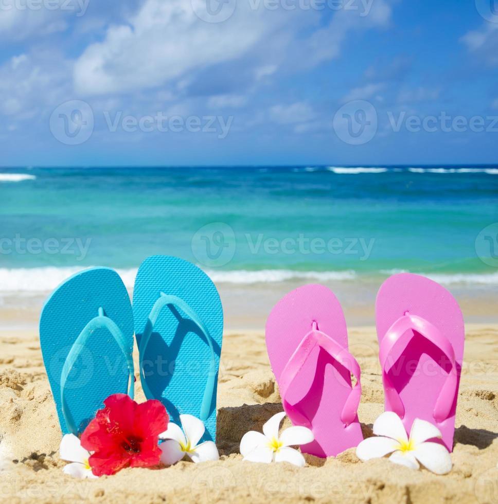 Flip flops on sandy beach photo
