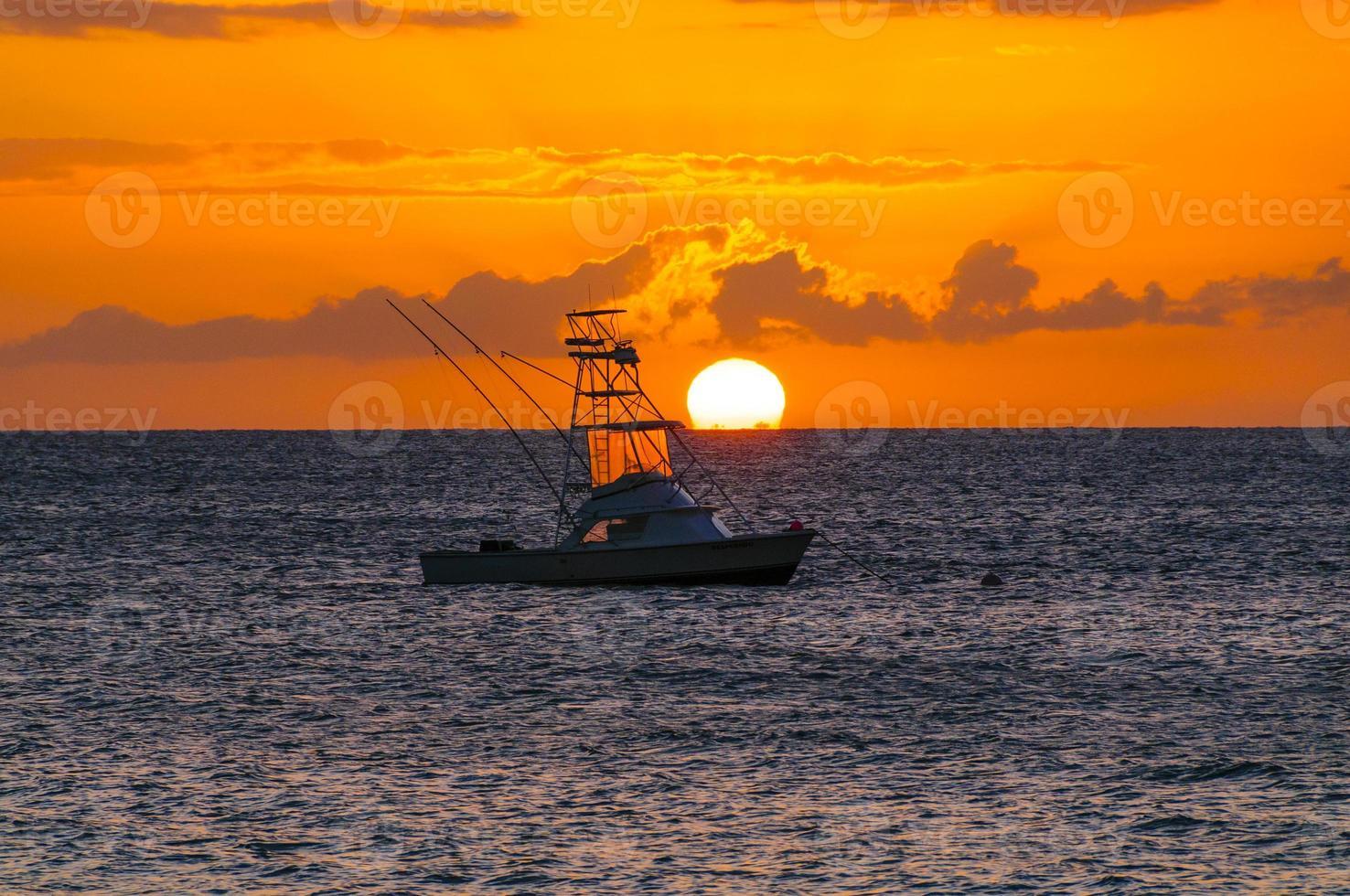 Hermosa puesta de sol detrás del barco de pesca deportiva en Maui, Hawaii, EE.UU. foto