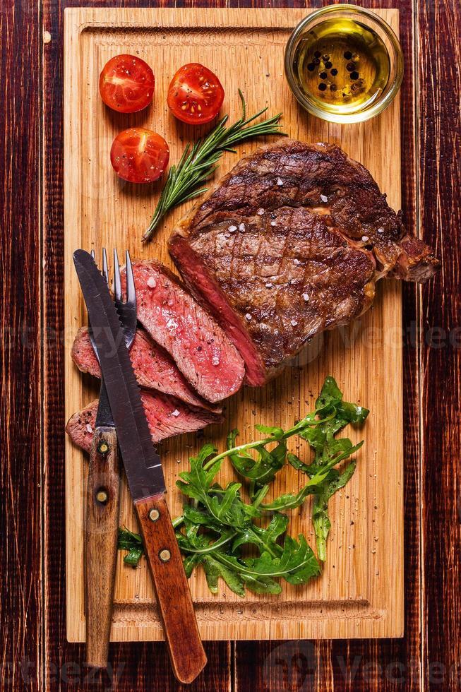 Ribeye steak with arugula and tomatoes. photo