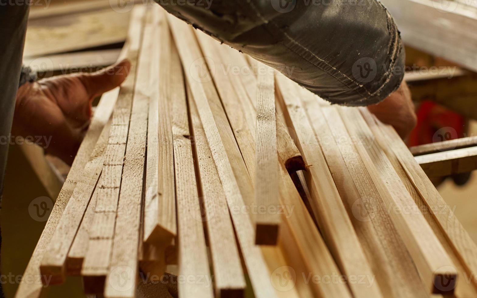 homem que trabalha com pranchas de madeira foto