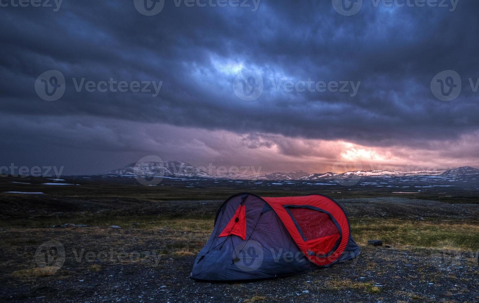 tienda de campaña en la montaña desnuda en la medianoche de verano foto