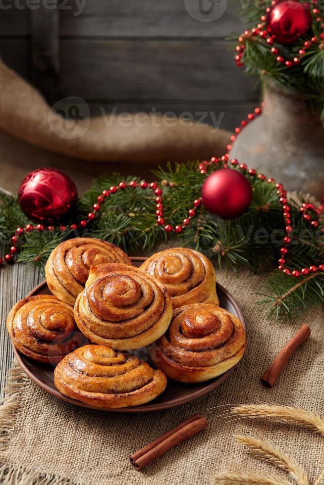 Cinnamon bun rolls christmas sweet dessert on vintage cloth with photo