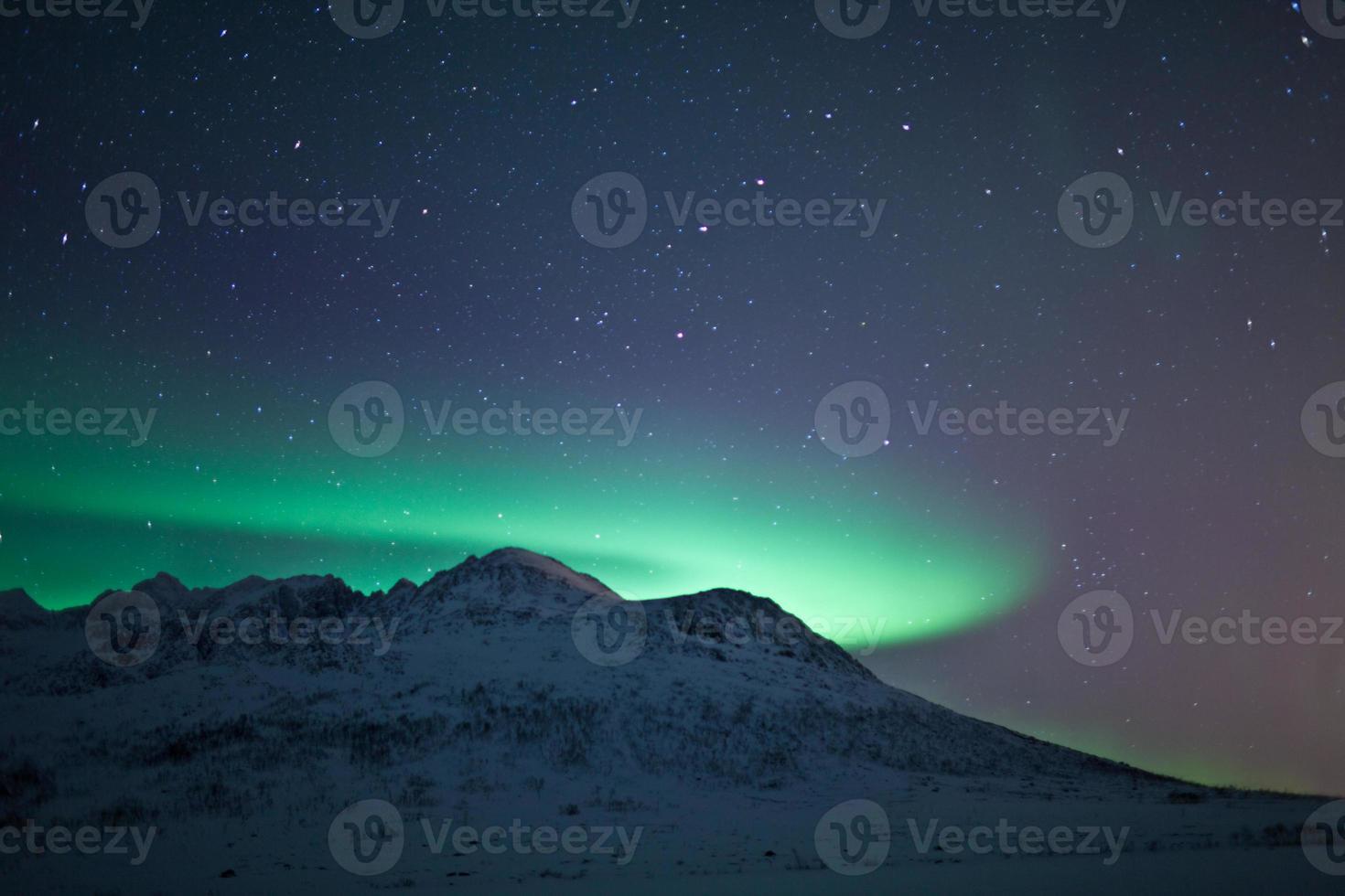 Aurora boreal detrás de una montaña foto