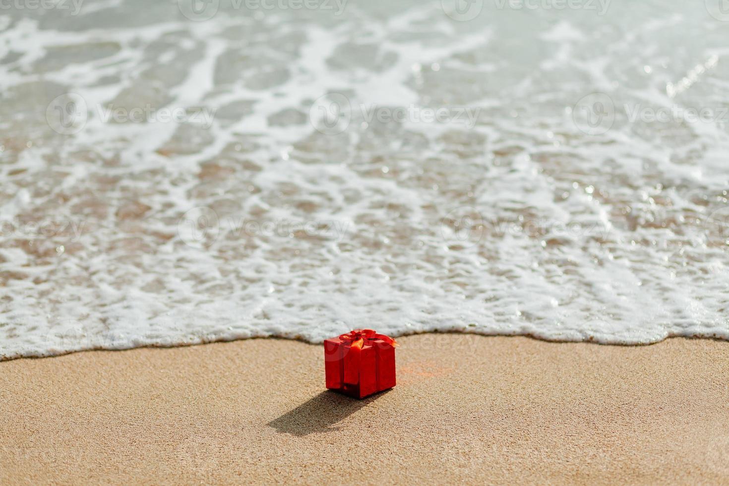 caixa de presente vermelha na praia foto