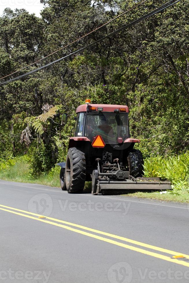 tractor tirando del accesorio de la cortadora de césped lateral de la carretera foto