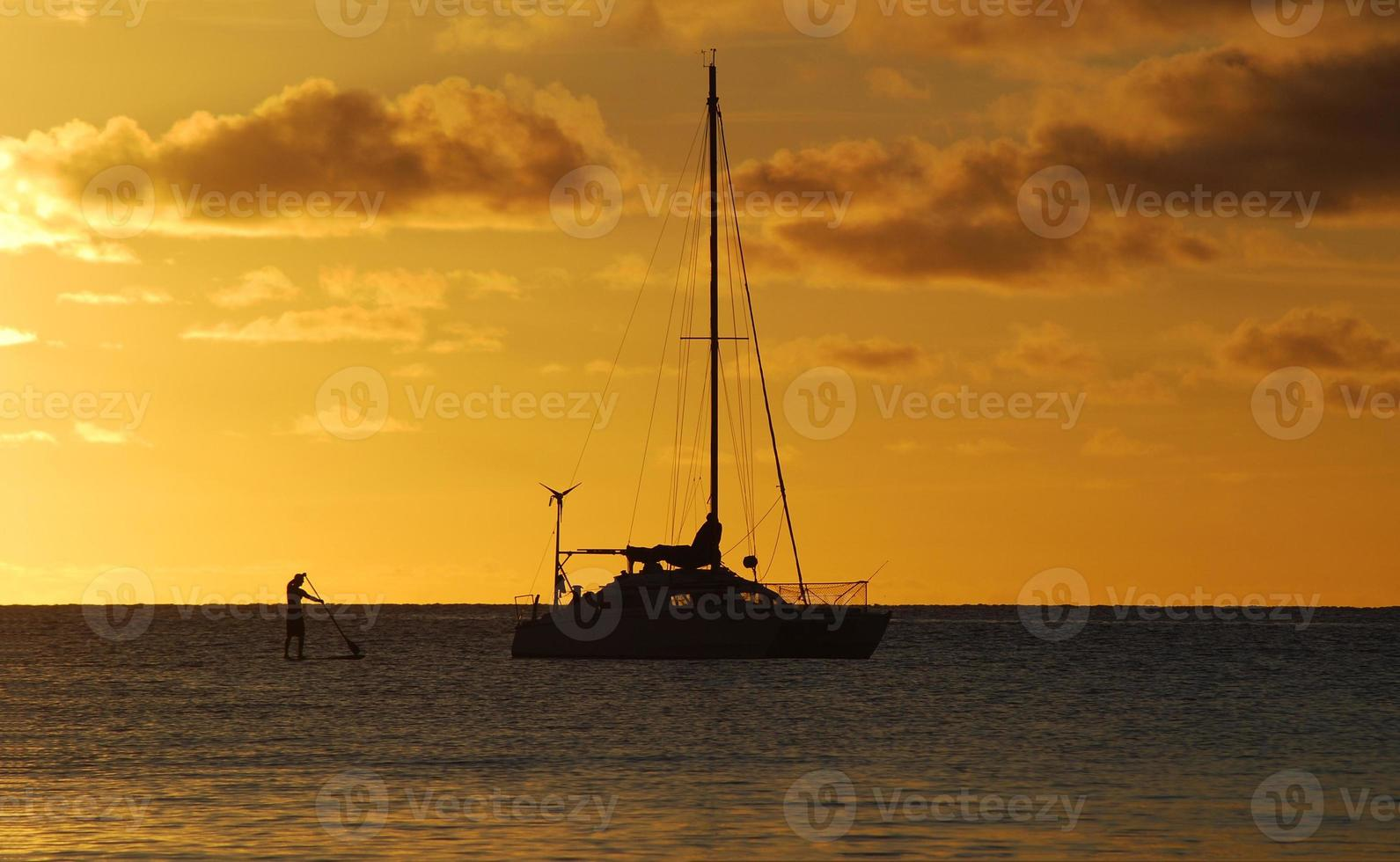 puesta de sol con catamarán y paddle-boarder foto