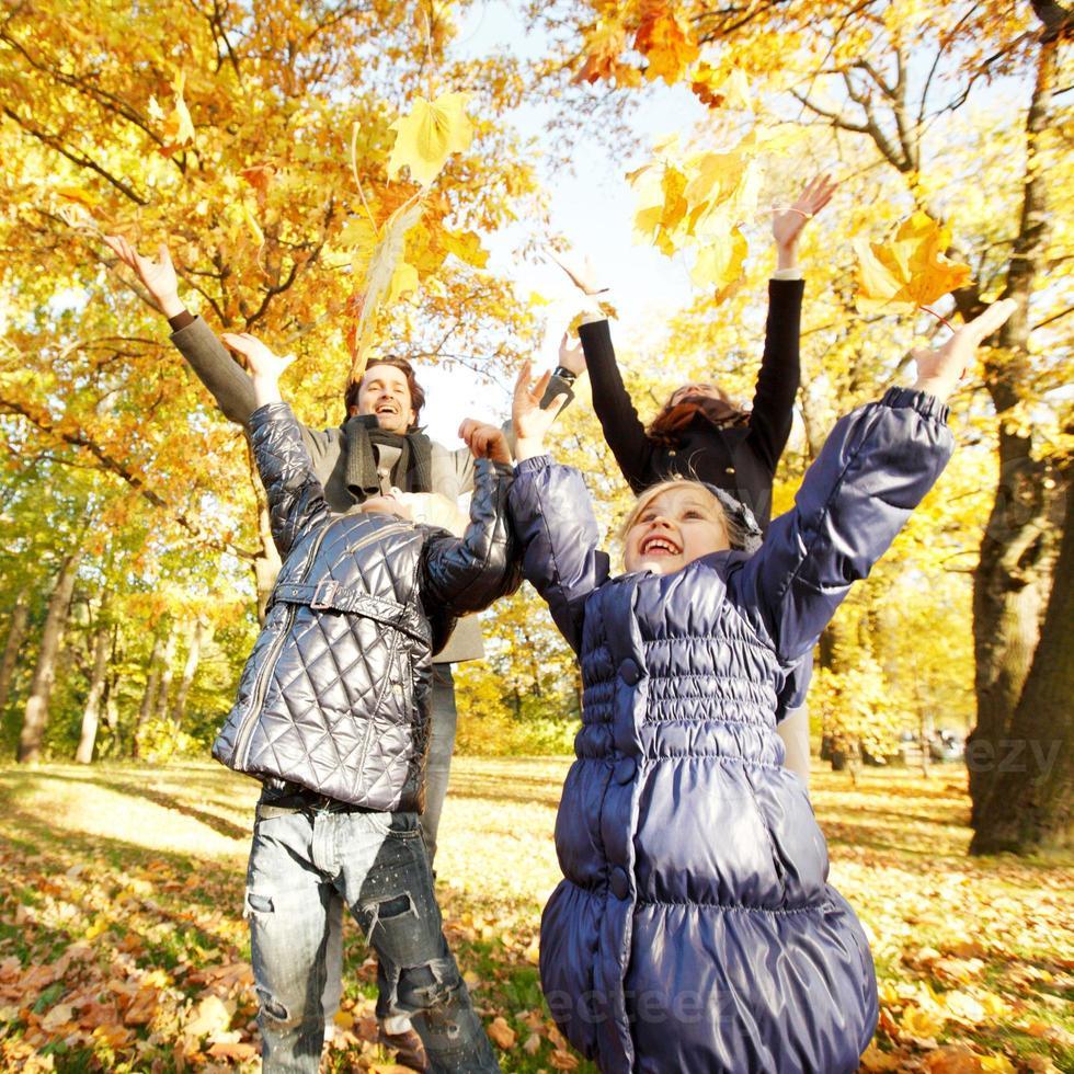família brincando com folhas de outono foto