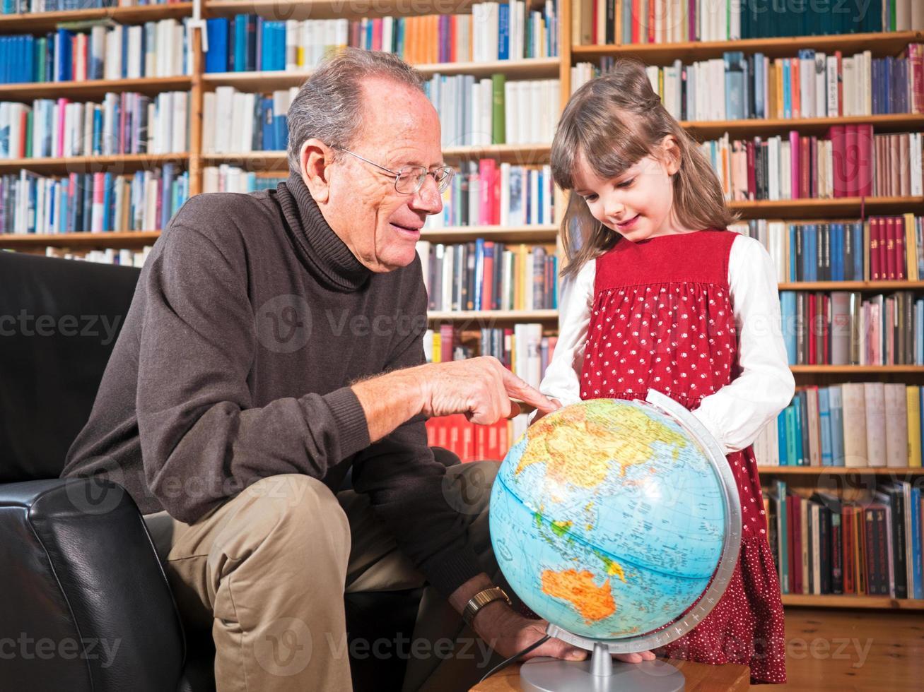 sênior e neta olhando para um globo foto