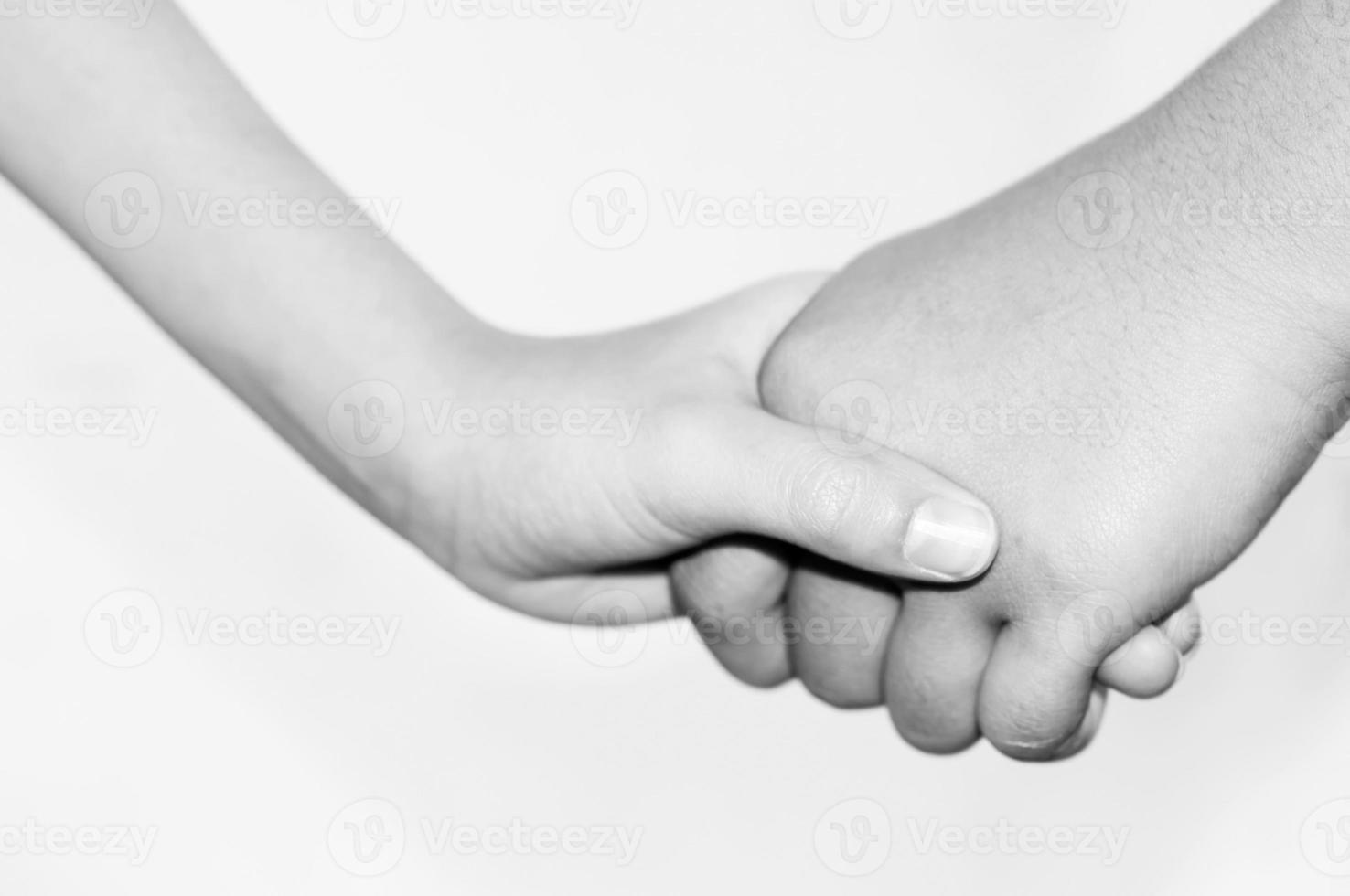 irmã mão segure seu irmão mais novo mão, preto e branco foto