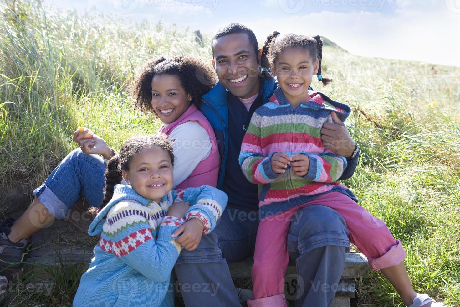 Retrato de familia sentada en el césped foto