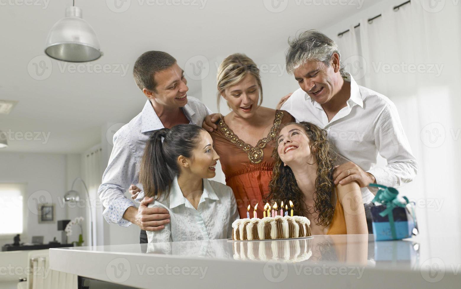 familia sentada alrededor de un pastel de cumpleaños foto