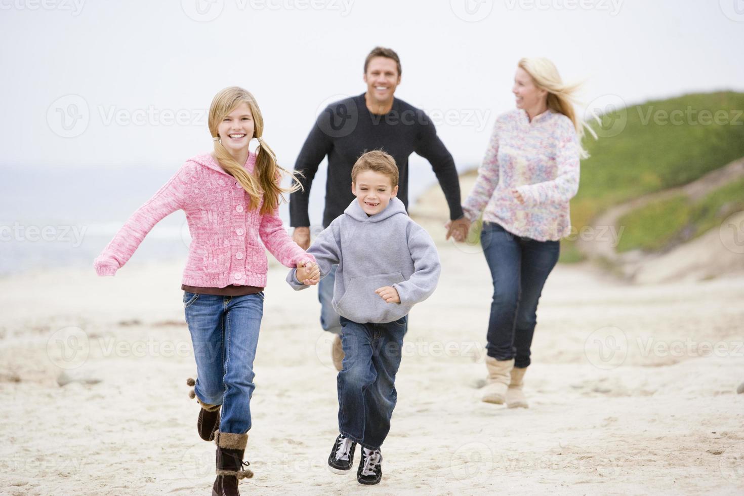 familia corriendo en la playa cogidos de la mano foto