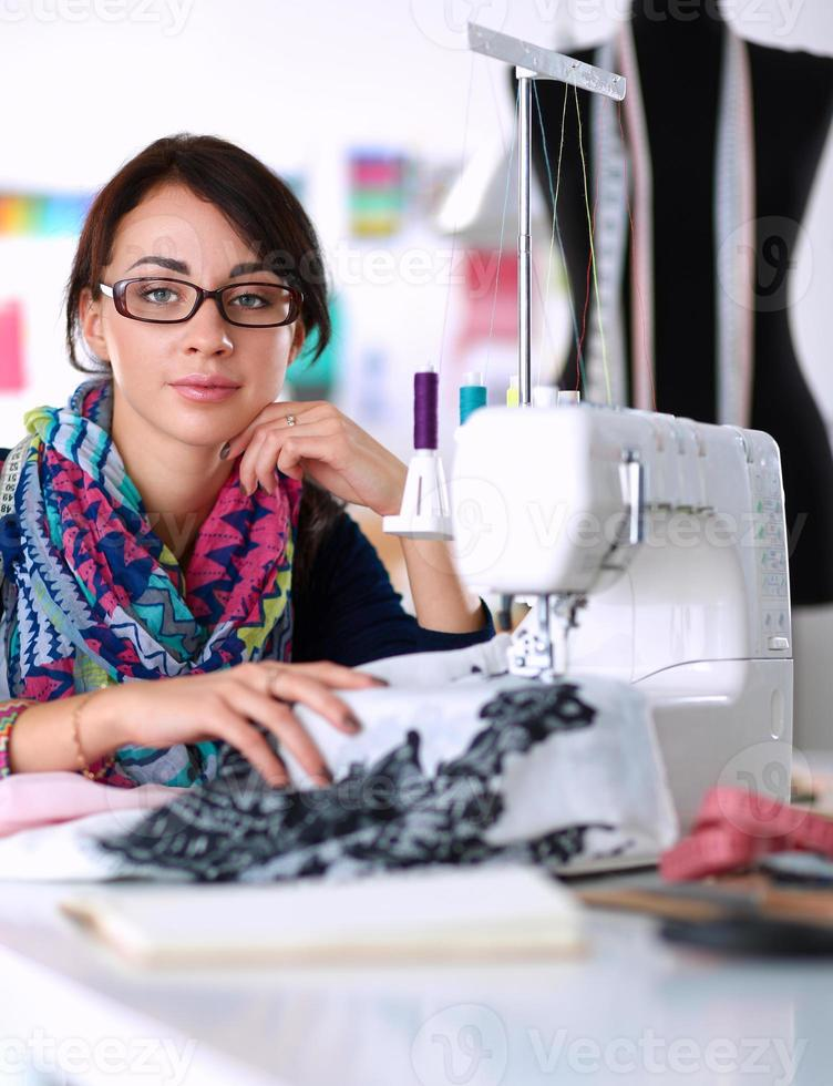mujer joven cosiendo mientras estaba sentado en su lugar de trabajo foto