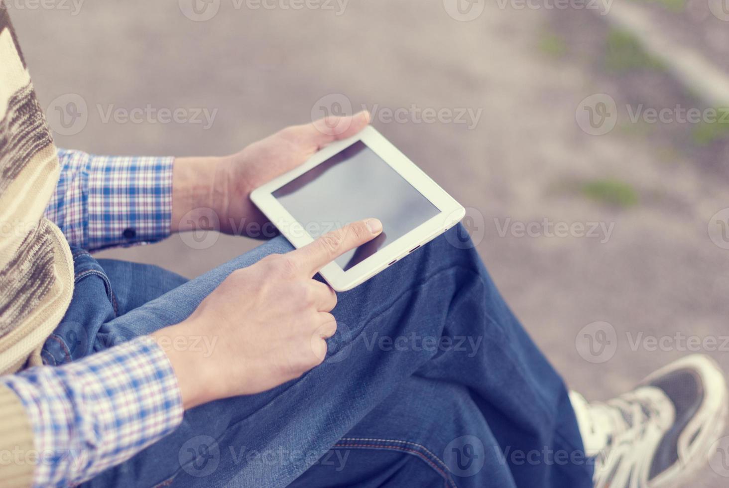 Hombre con tableta en mano en la calle. foto
