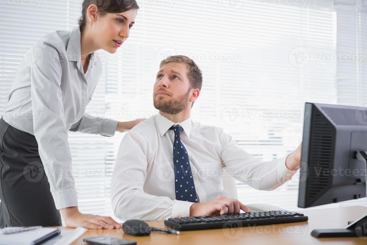 empresario mostrando a su compañero de trabajo algo en la computadora foto