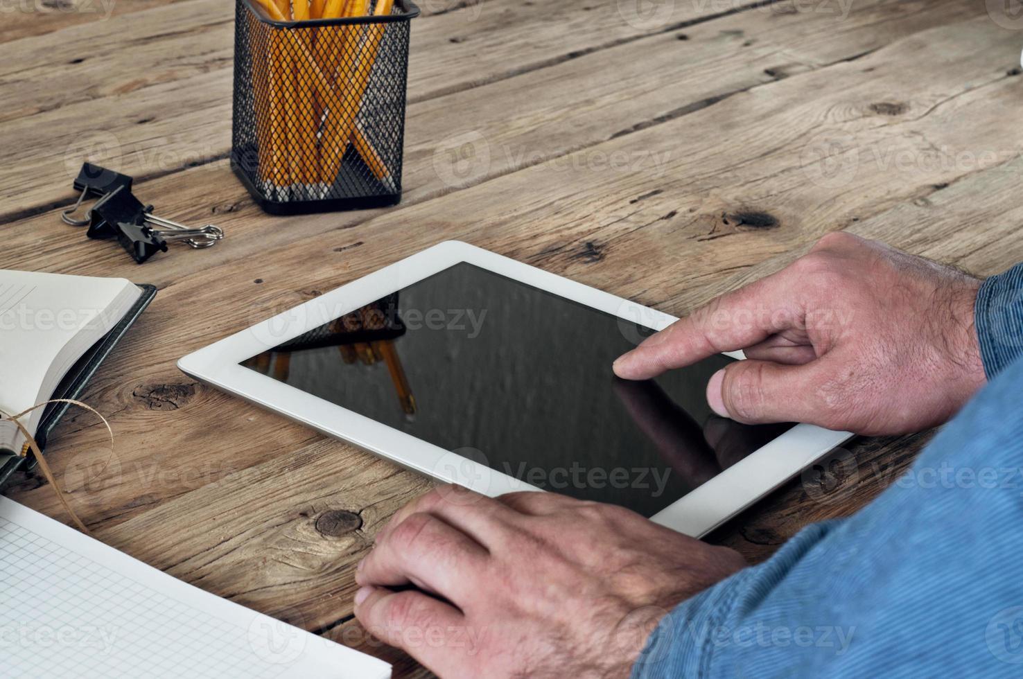 el hombre hace clic en la tableta de la pantalla en blanco foto