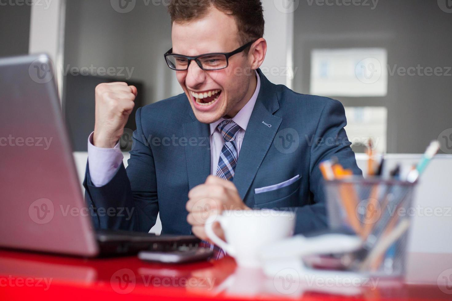 joven empresario feliz con la computadora portátil en la oficina. foto