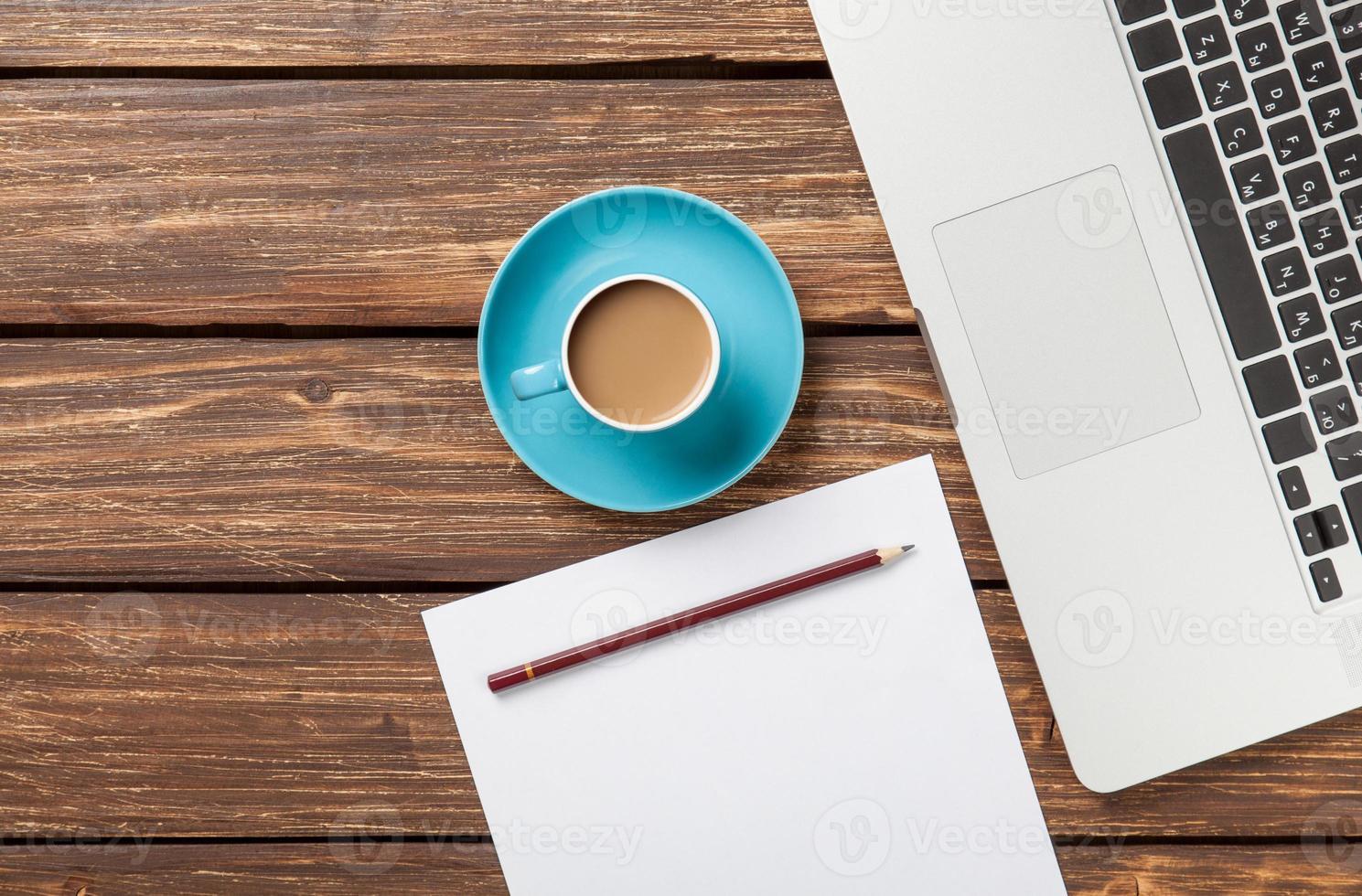 taza de café y papel con computadora portátil foto