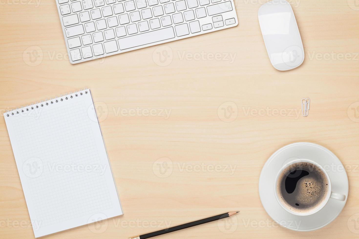 mesa de oficina con bloc de notas, computadora y taza de café foto