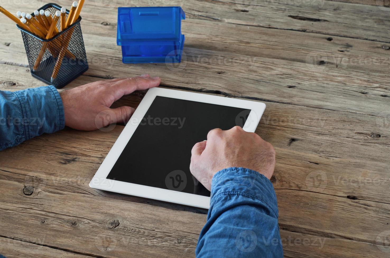 Hombre trabajando en casa usando una tableta foto