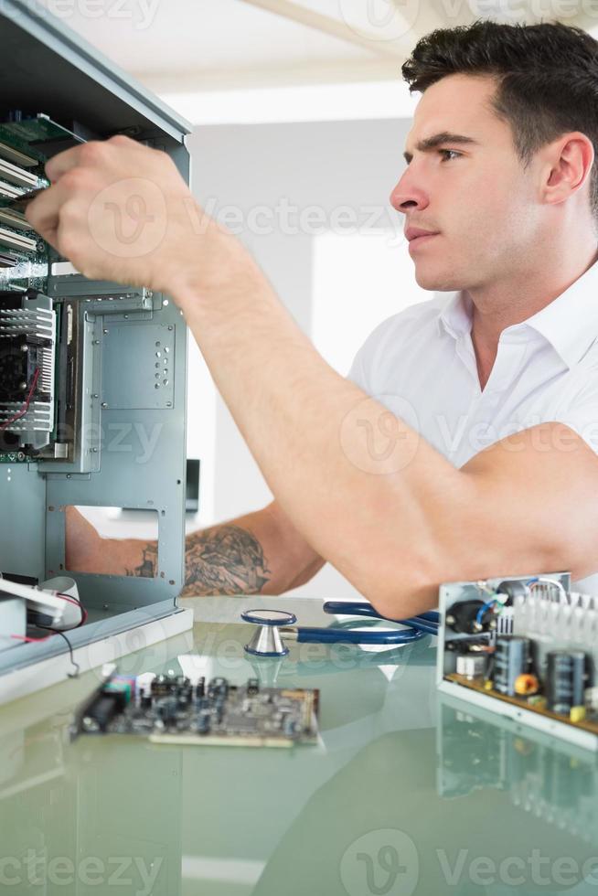 ingeniero informático severo guapo trabajando en pc abierto foto