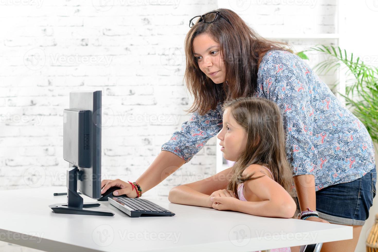 joven maestra ayuda a una colegiala en una computadora foto