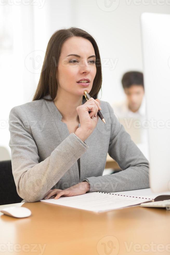 Retrato de empresaria trabajando en la computadora en la oficina foto