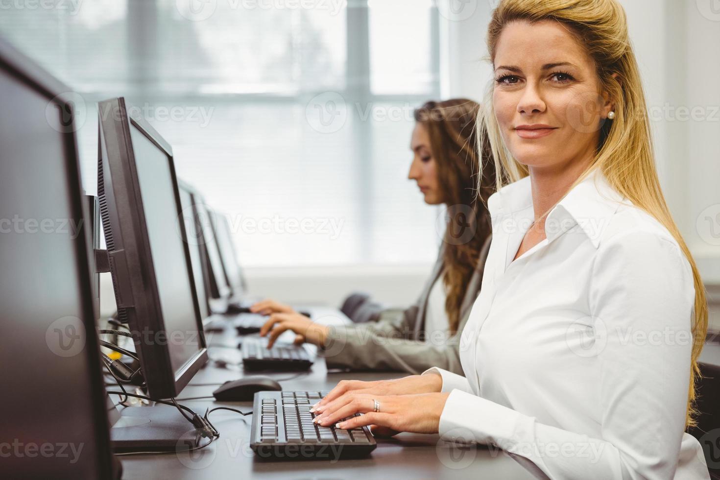 mujer feliz en sala de computación sonriendo a la cámara foto