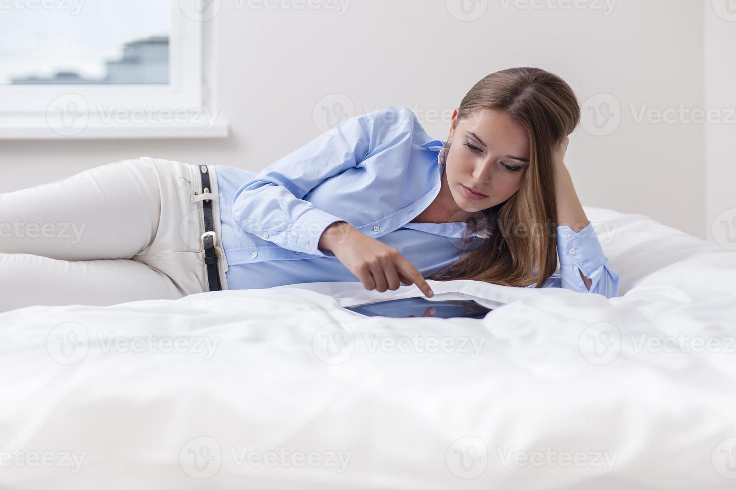 hermosa mujer usando tableta en su cama foto