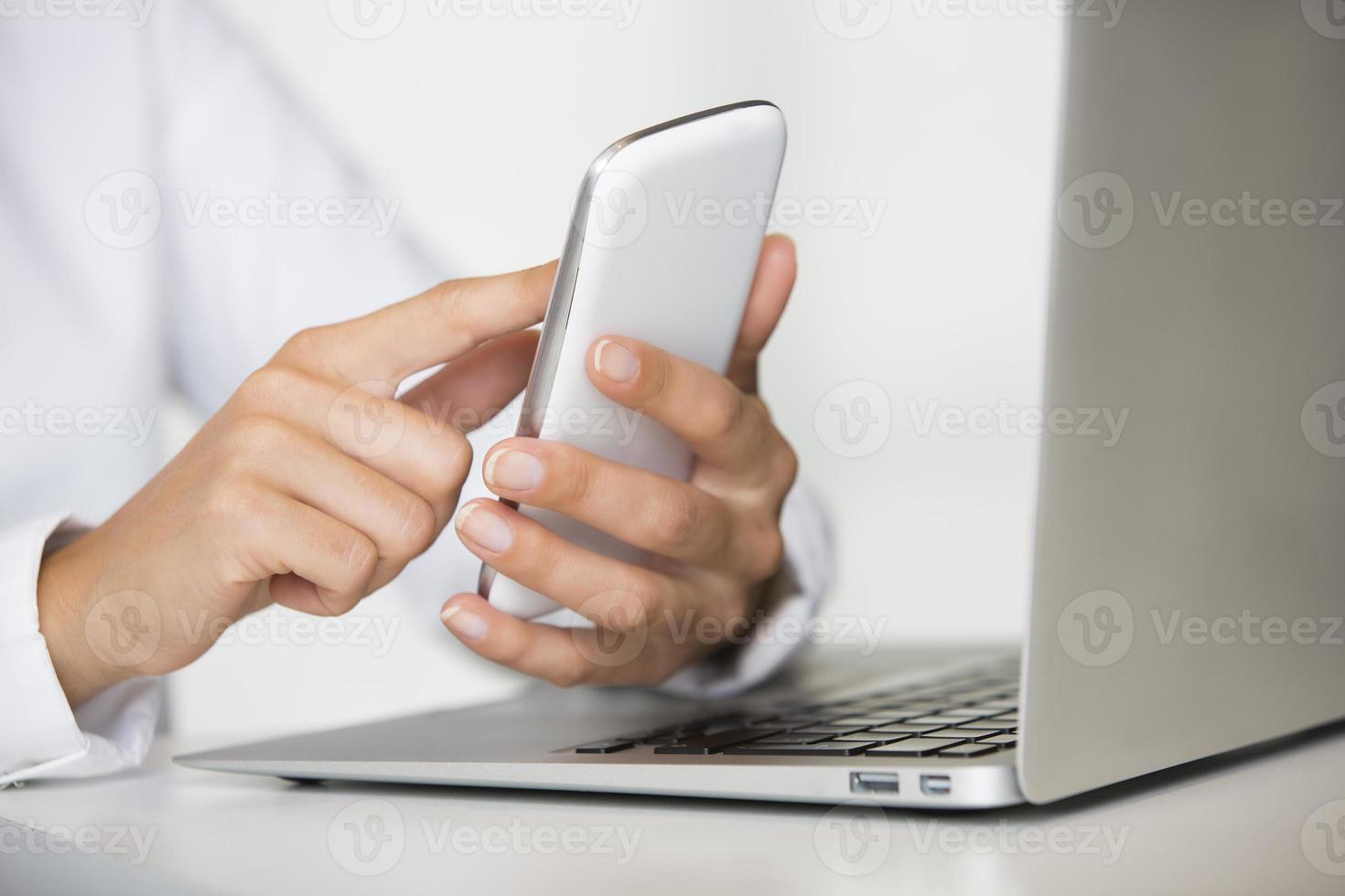 manos femeninas que sostienen el teléfono inteligente delante de la computadora portátil foto