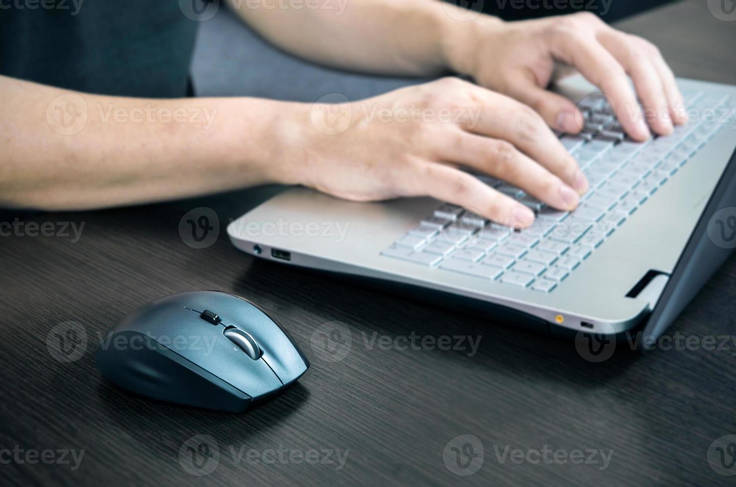 Hombre usando laptop con teclado blanco. trabajando en la oficina foto