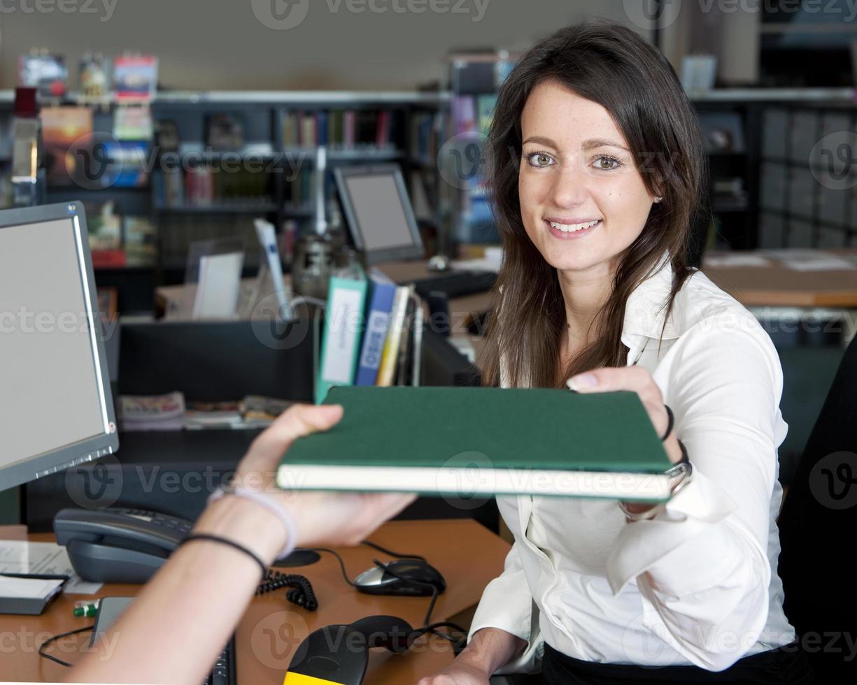 señorita delante de una computadora que recibe un libro foto