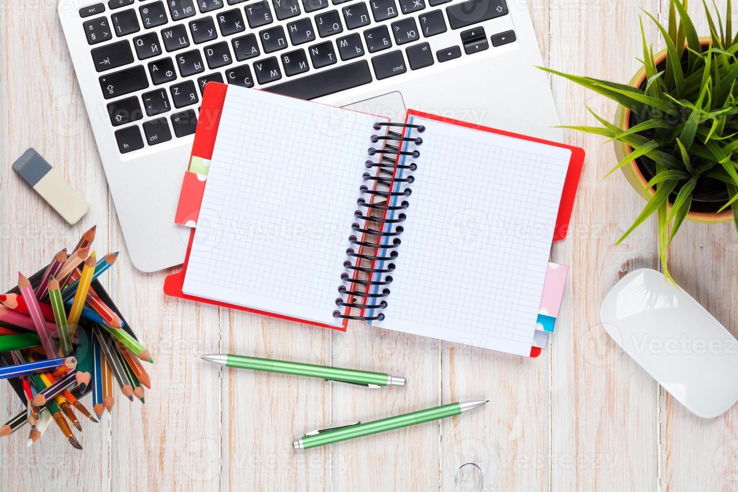 mesa de escritorio de oficina con computadora, suministros y flores foto