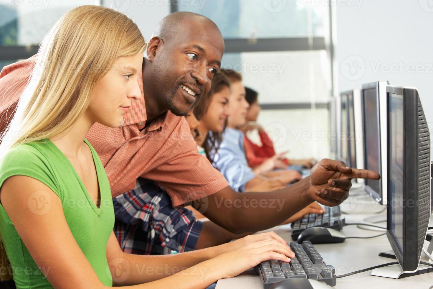 Profesor ayudando a los estudiantes que trabajan en computadoras en el aula foto