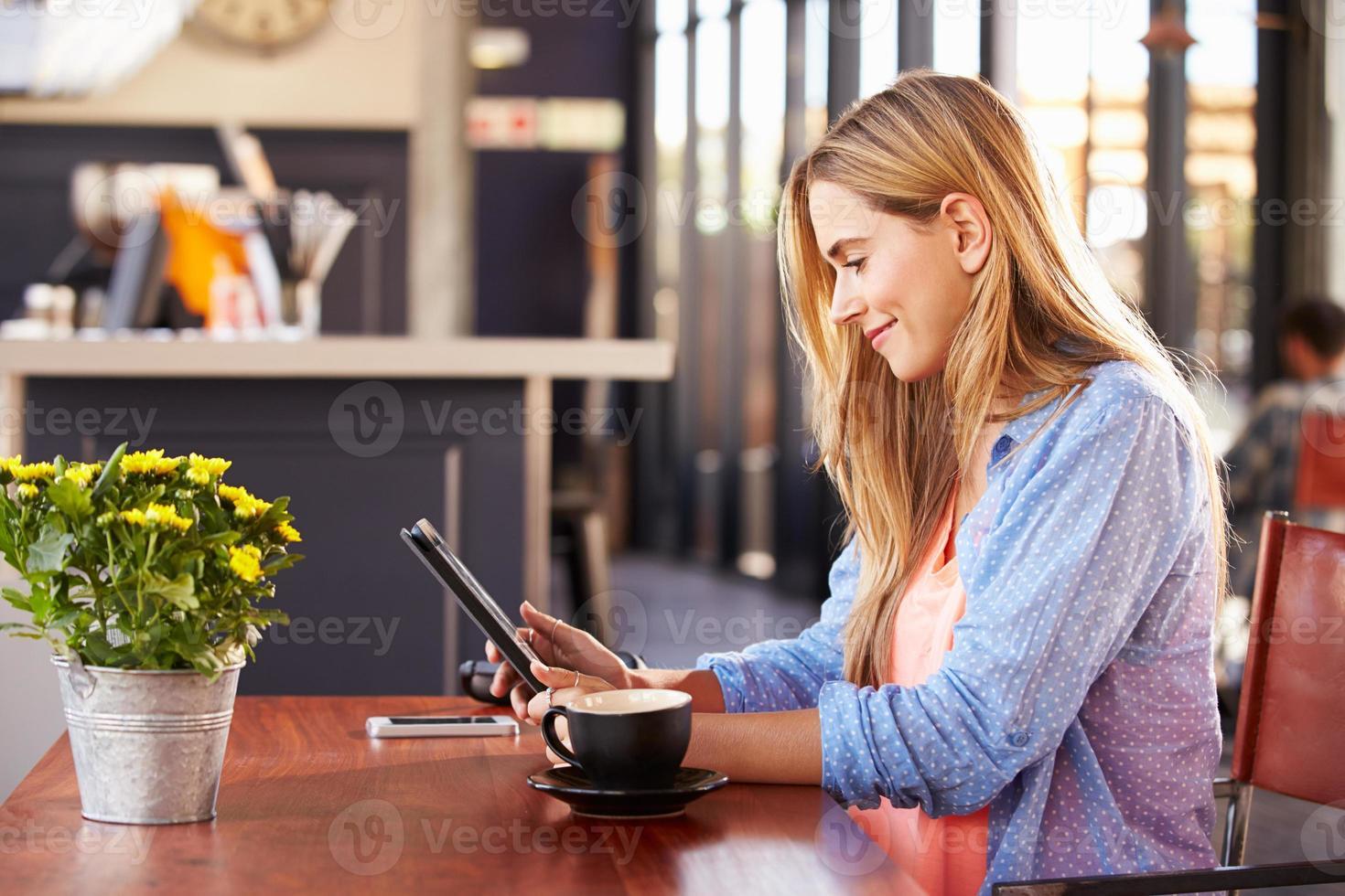mujer joven con computadora en una cafetería foto