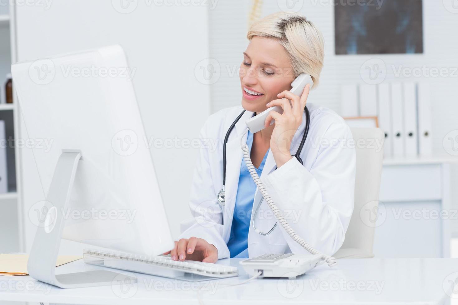 médico de guardia mientras usa la computadora en la clínica foto