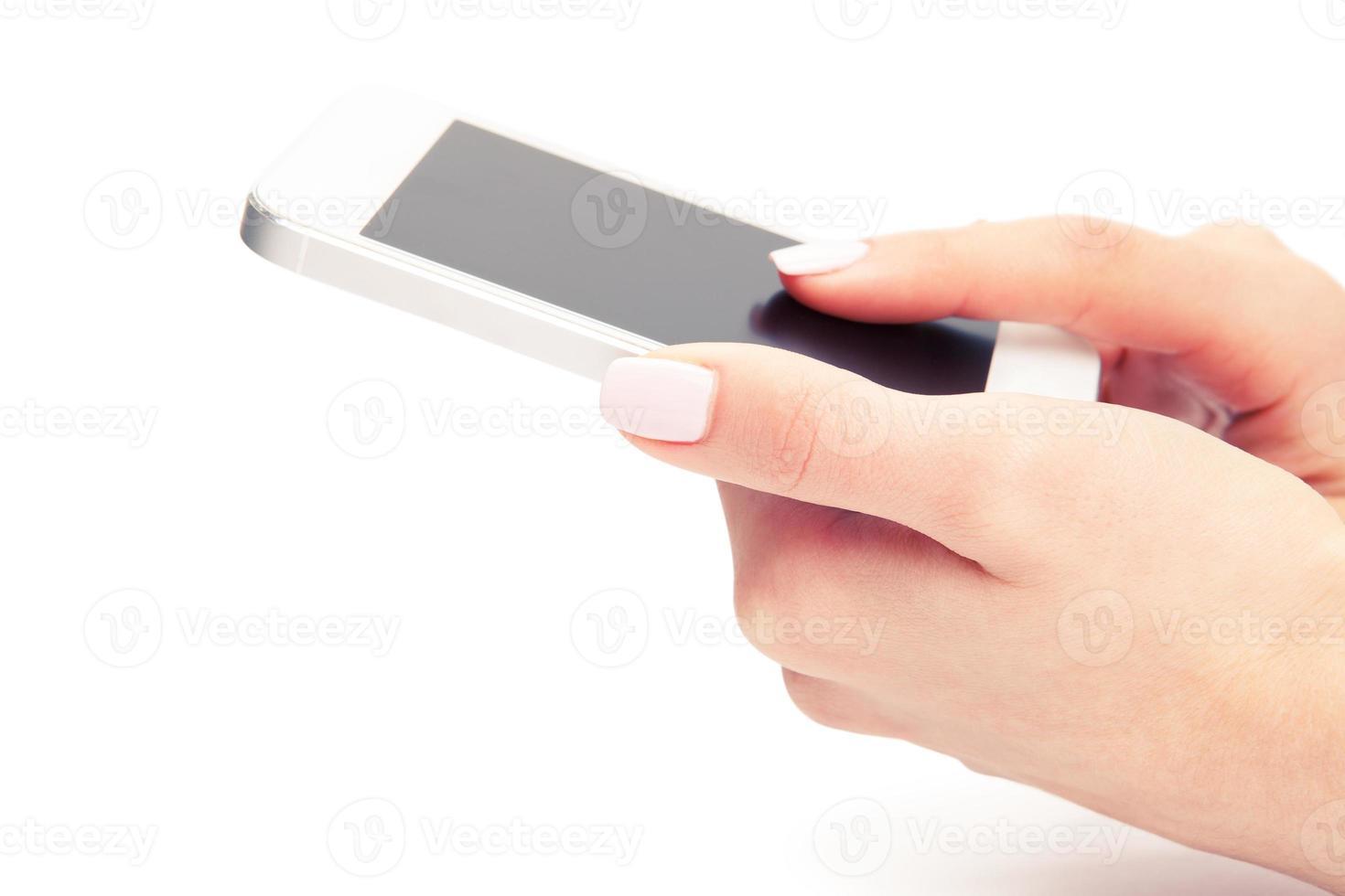 Mano que sostiene el teléfono inteligente blanco con pantalla en blanco sobre blanco centrico foto