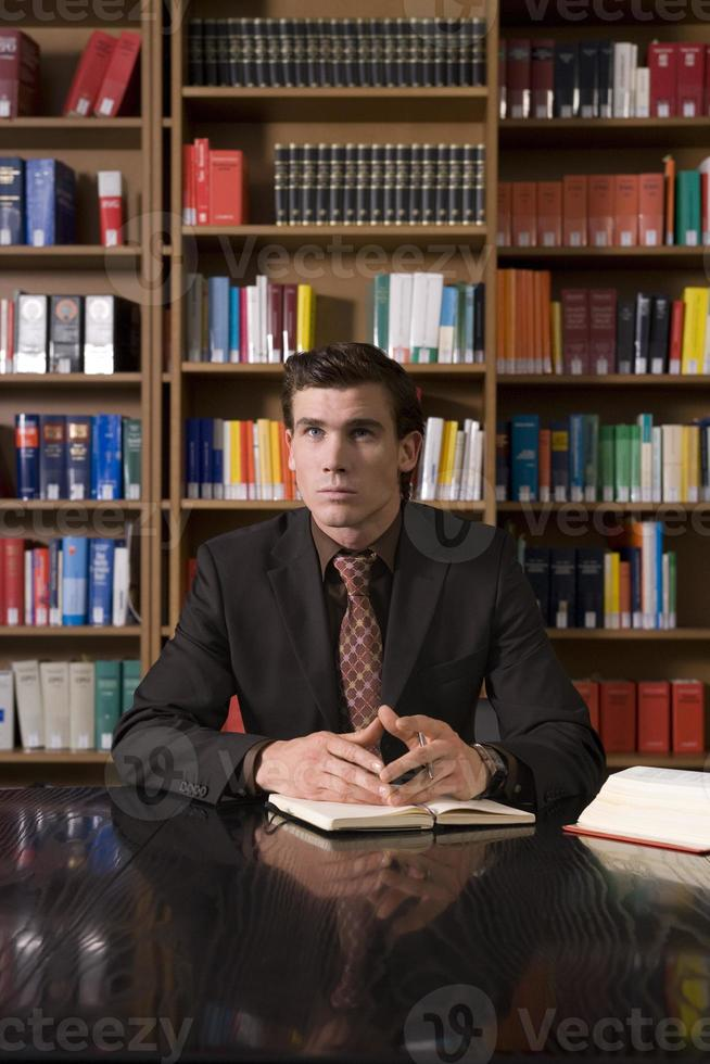 hombre pensativo en el mostrador de la biblioteca foto
