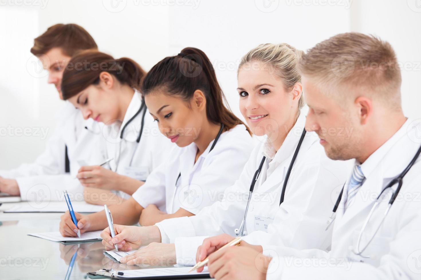 fila de médicos escribiendo en el escritorio foto