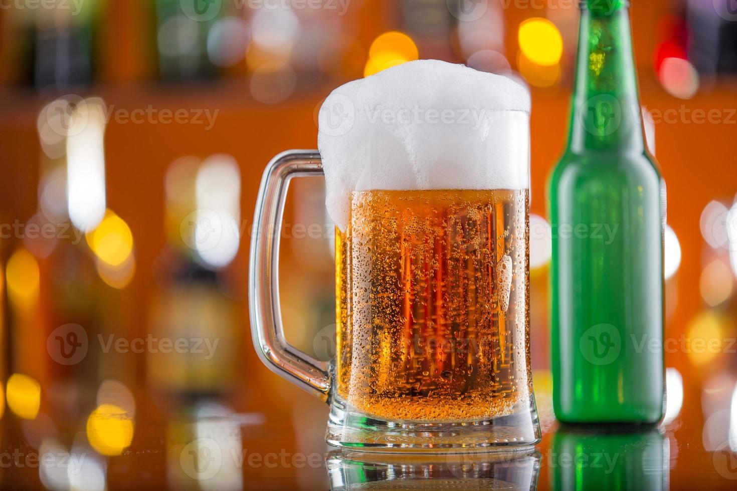 Botella de cerveza con vaso en la barra de escritorio foto