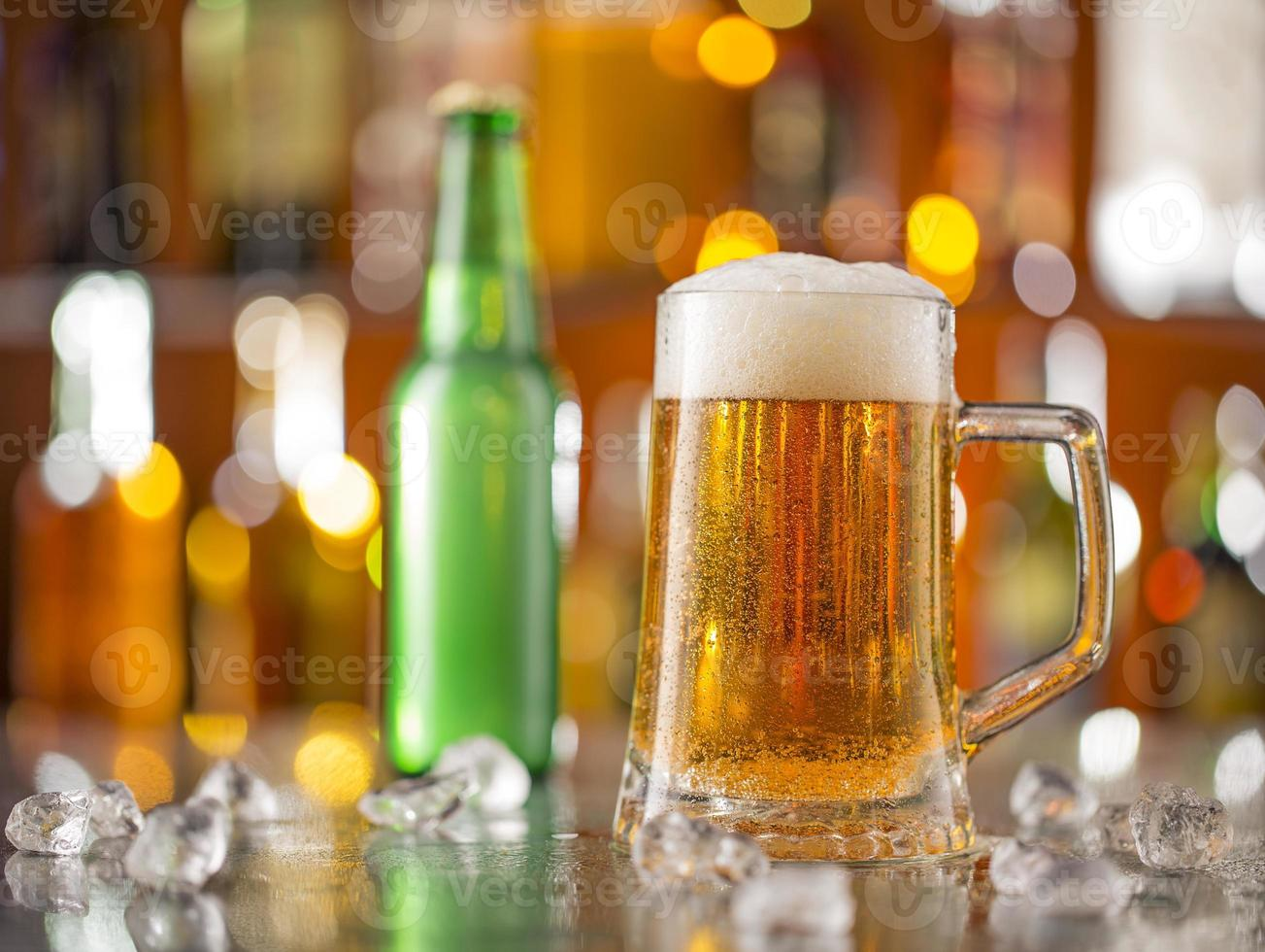 Bottle of beer with glass on bar desk photo