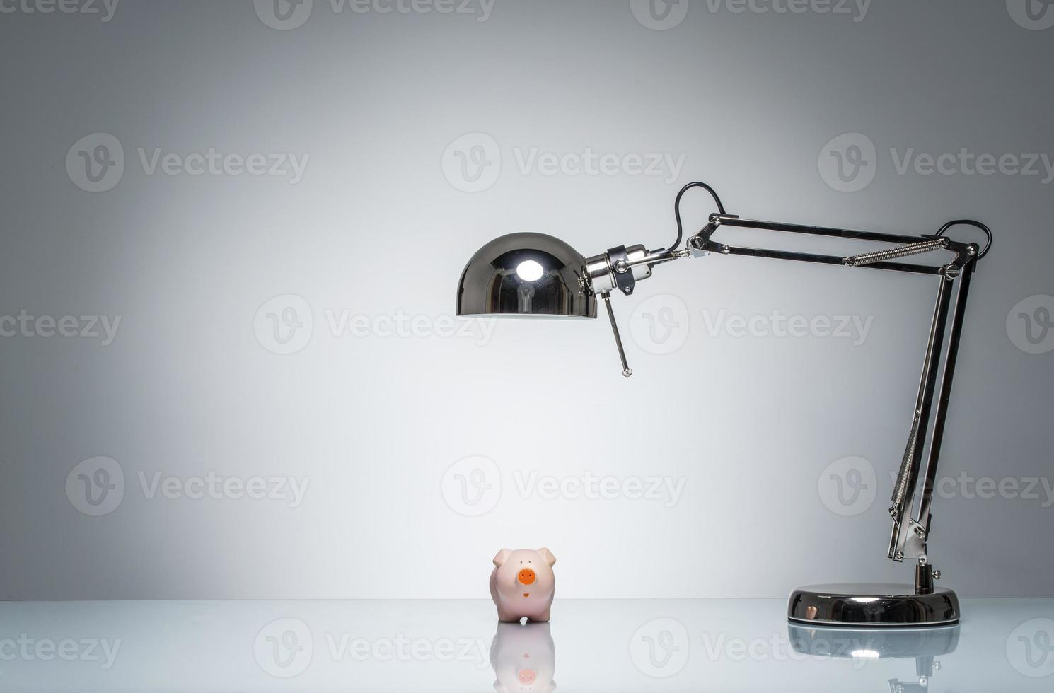 iluminando hucha rosa con lámpara de escritorio foto
