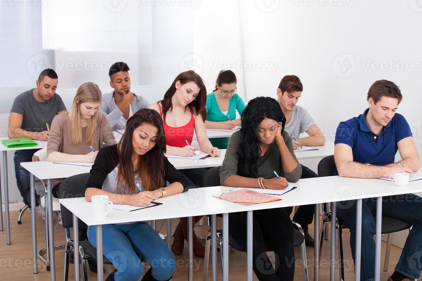 estudiantes universitarios escribiendo en el escritorio foto