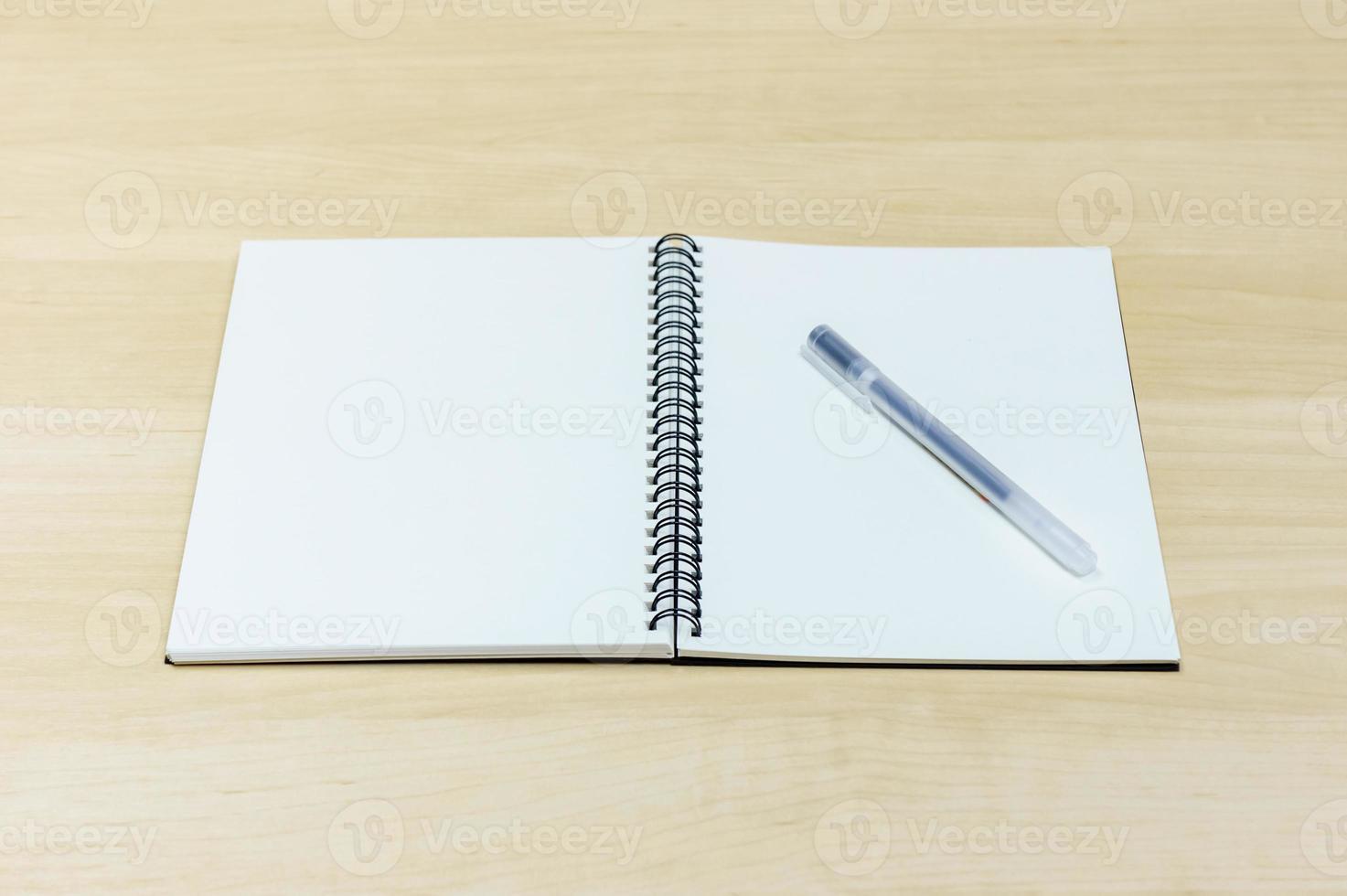 bolígrafo y cuaderno sobre escritorio de madera foto