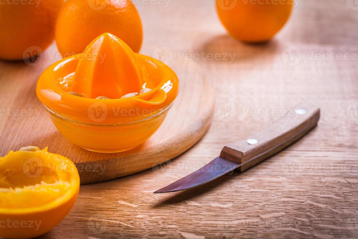 Exprimidor naranja cuchillo en escritorio de madera foto