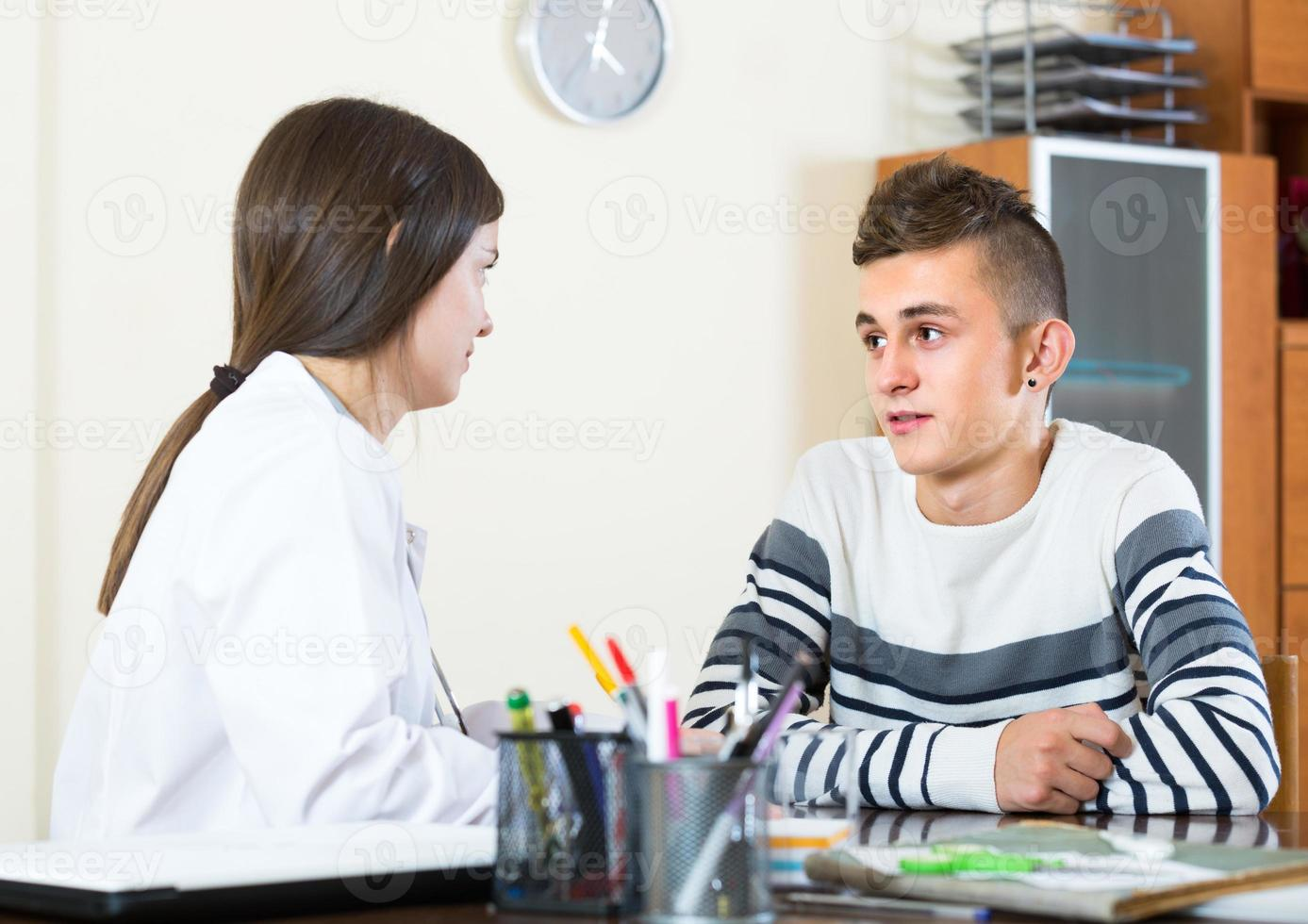 Teenager and doctor at desk in clinic photo