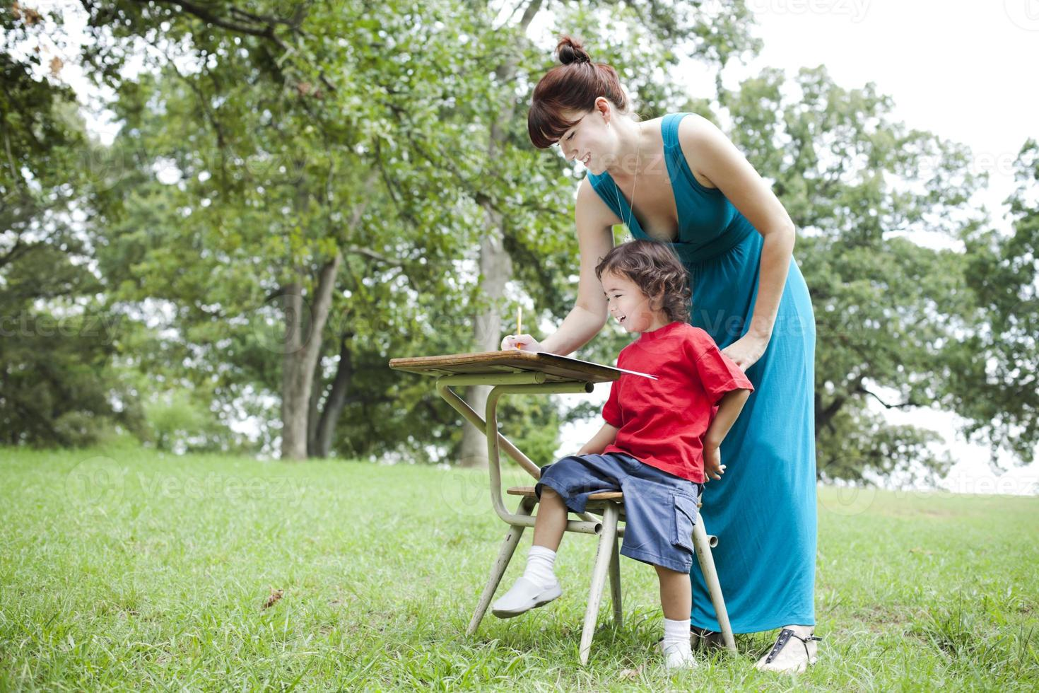 Little Boy and Woman at Desk Outdoors photo