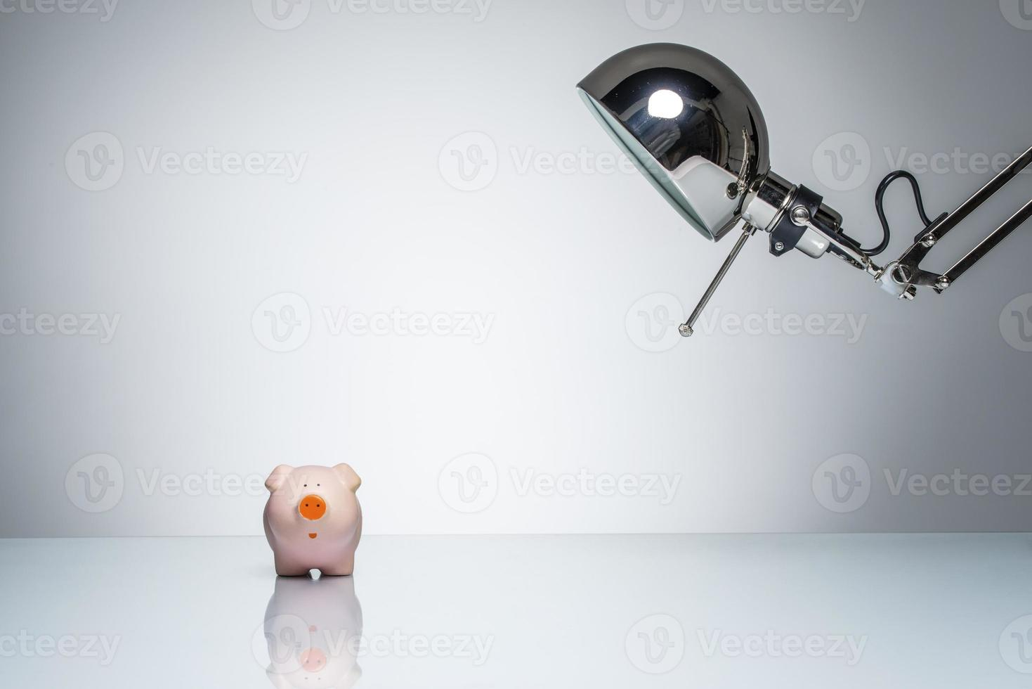 lighting up pink piggy bank with desk lamp photo