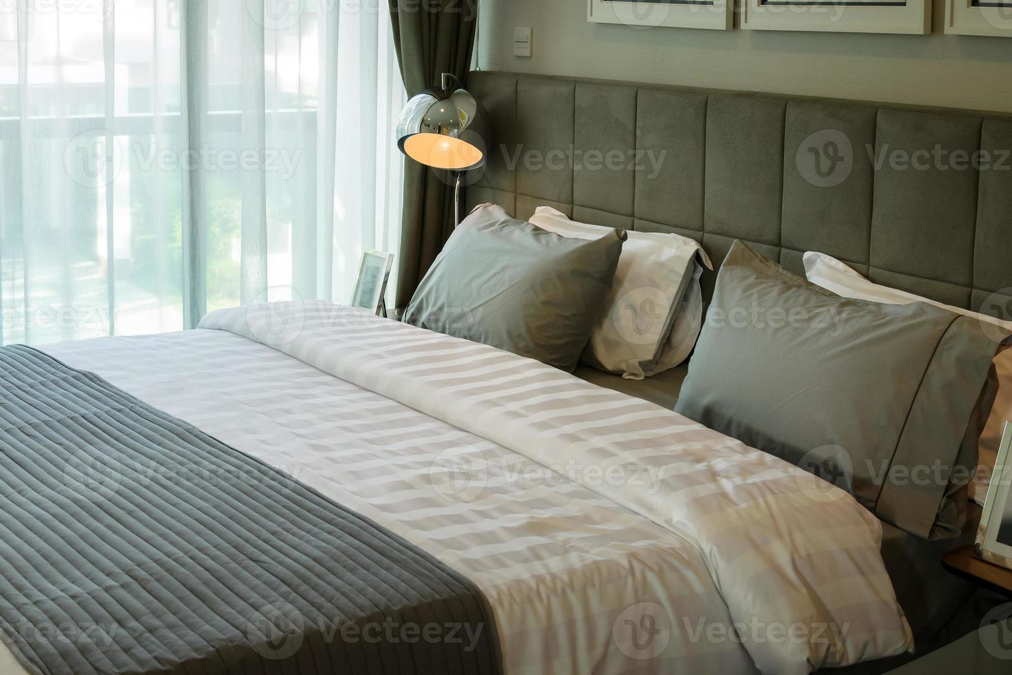 lámpara de escritorio de metal y almohada gris en la cama foto