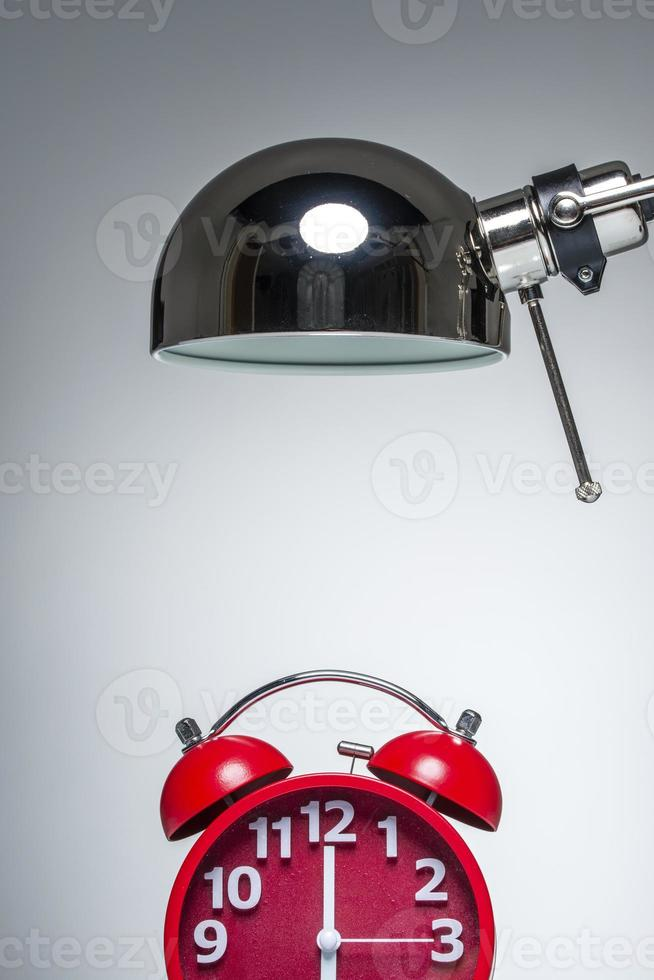 lighting up red alarm clock with desk lamp photo